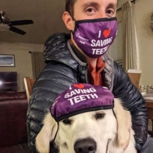 """A man and his dog are wearing purple """"I heart saving teeth"""" face masks. The man has the mask covering his nose and mouth, while the dog's mask is on the top of his head"""