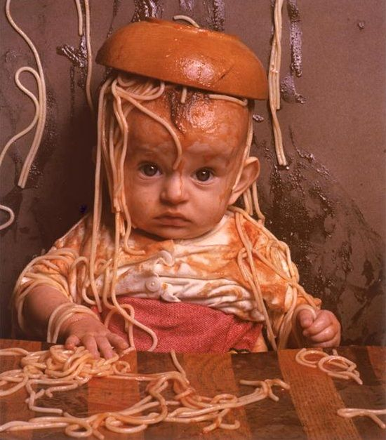 child with bowl of spaghetti upside down on head
