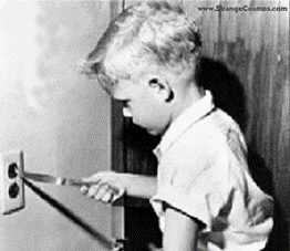 Boy putting knife in electric outlet