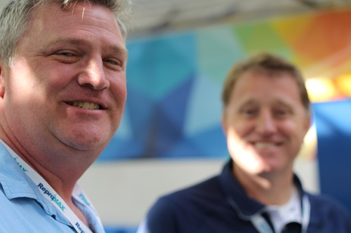An image of two grown men smiling at a camera with one mans face blurred out a little bit