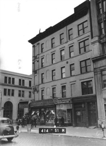 Delancey Street facade of 103 Orchard, looking southeast, showing two stores with different infill at left, and ornamental entrance surround at apartment and easement entries at right. Brickwork and terra cotta on upper floors are painted a uniform light color. ca. 1940 | Credit: NYC Municipal Archives via Lower East Side Tenement Museum