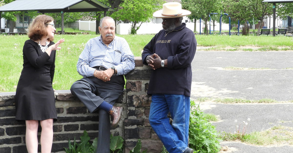 Three people leaning against a brick wall with a grassy area behind them. The center individual is leaning facing forward while the other two are in profile view. They are having a conversation.