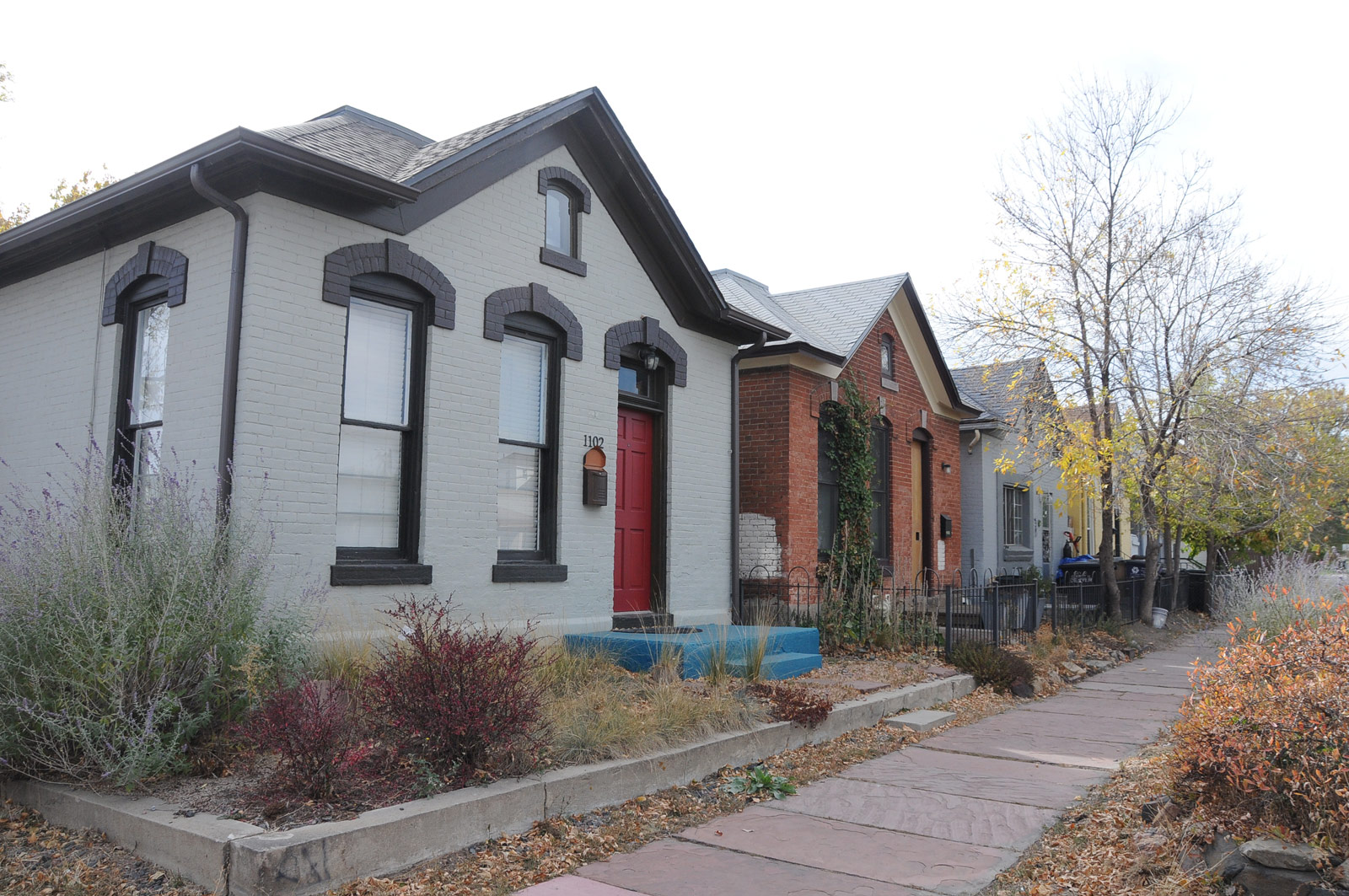 A row of Italianate Cottages. The red brick second house in, is where a Chicana leader, Josie Acosta, grew up as a little girl.