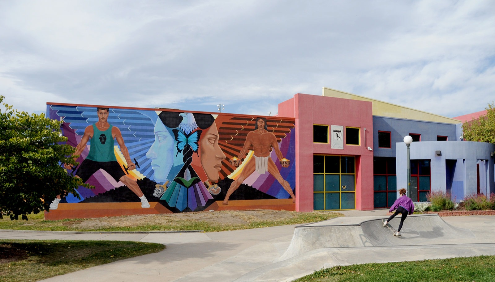 """La Alma"""" mural by Emanuel Martinez on the Recreation Center in La Alma Lincoln Park. The mural shows two outward faces flanked by two images of two figures standing wide legged. The mural shows a then and now story of the neighborhood."""