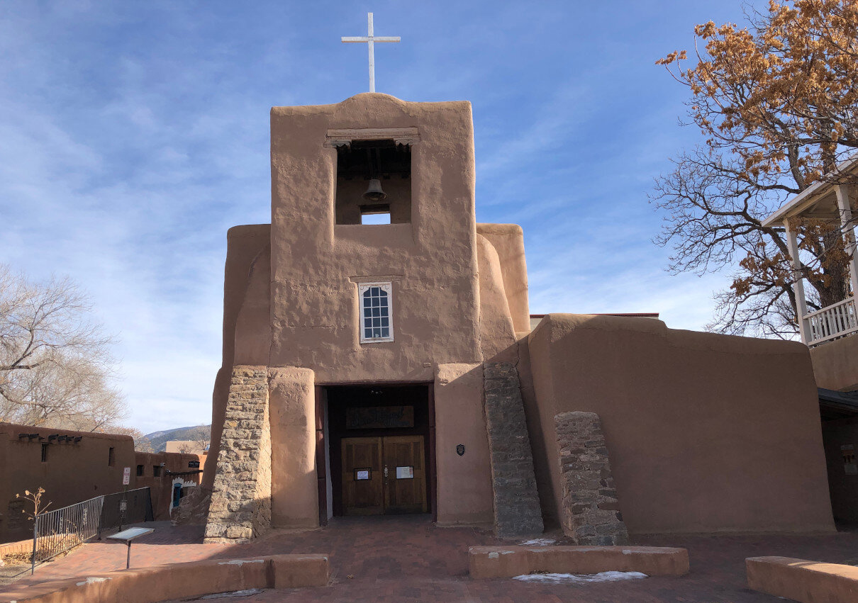 Exterior view of the San Miguel Chapel in Santa Fe. There is a courtyard in front and trees flanking the building and a cross on the top of the church.
