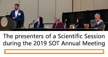 The speakers for a 2019 Scientific Session stand and sit behind a podium and long table on a dais