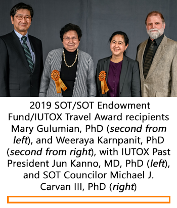 Four smiling individuals stand posed in front of the camera. Two women stand in the middle with rosette ribbons pinned to their lapels; they are the recipients of SOT/SOT Endowment Fund/IUTOX Travel Award recipients.