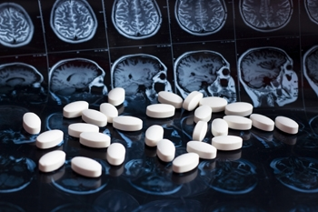 An image contacting x-rays of brains in the background. In the foreground, pills lay on a table.