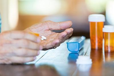Older hand holding pills