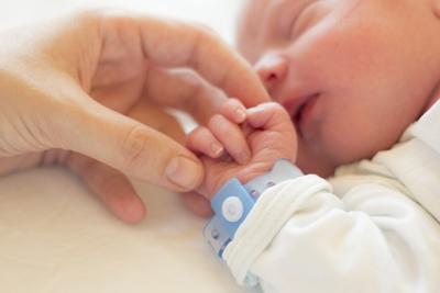 Newborn in hospital holding woman's hand