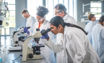 In the foreground, a young woman in a lab coat stands at a lab bench. She is leaning over and looking into a microscope. In the background, other men and women are visible and also working at scientific tasks.