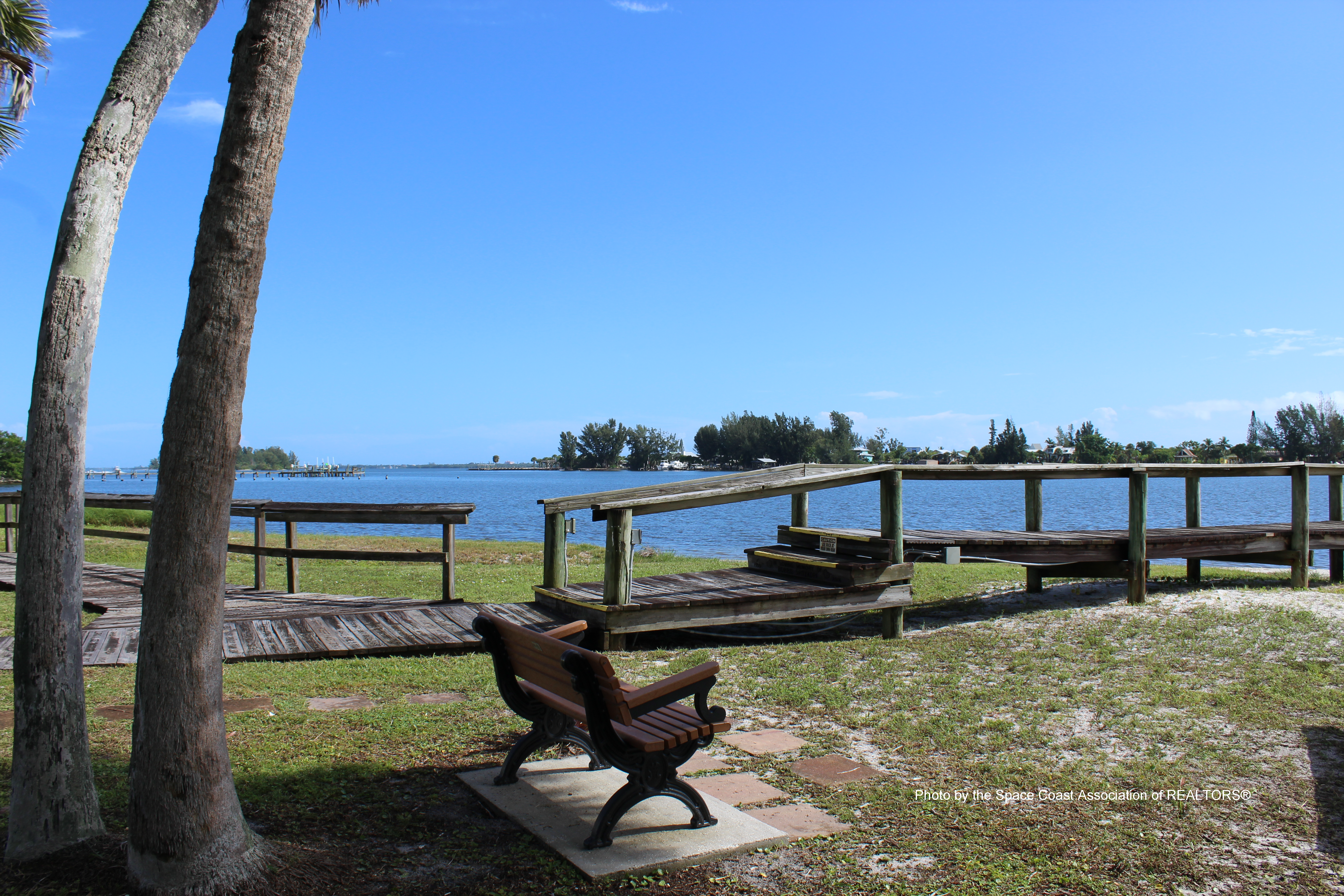 Bench overlooking Fisherman's Landing beneath palm trees at Grant-Valkaria